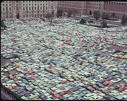 Parking lot in what is now the Reagan Building. Commerce Department in background on right. (1974)