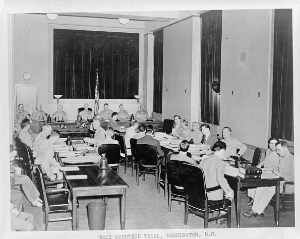 Nazi saboteur trial, Washington, D.C. The special seven-man military commission opens the third day of its proceedings in the trial of eight Nazi saboteurs in the fifth floor courtroom of the Department of Justice building. Sitting on the commission left to right are: Brigadier General John T. Lewis; Major General Lorenzo D. Casser; Major General Walter S. Grant; Major General Frank R. McCoy, president of the commission; Major General Blanton Winship; Brigadier General Guy V. Henry; Brigadier General John T. Kennedy. (Wikipedia)
