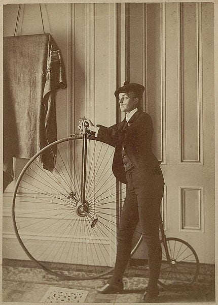 Self-portrait by Johnston, dressed as a man, sporting a fake mustache and holding a bicycle, ca. 1890 (Wikipedia)