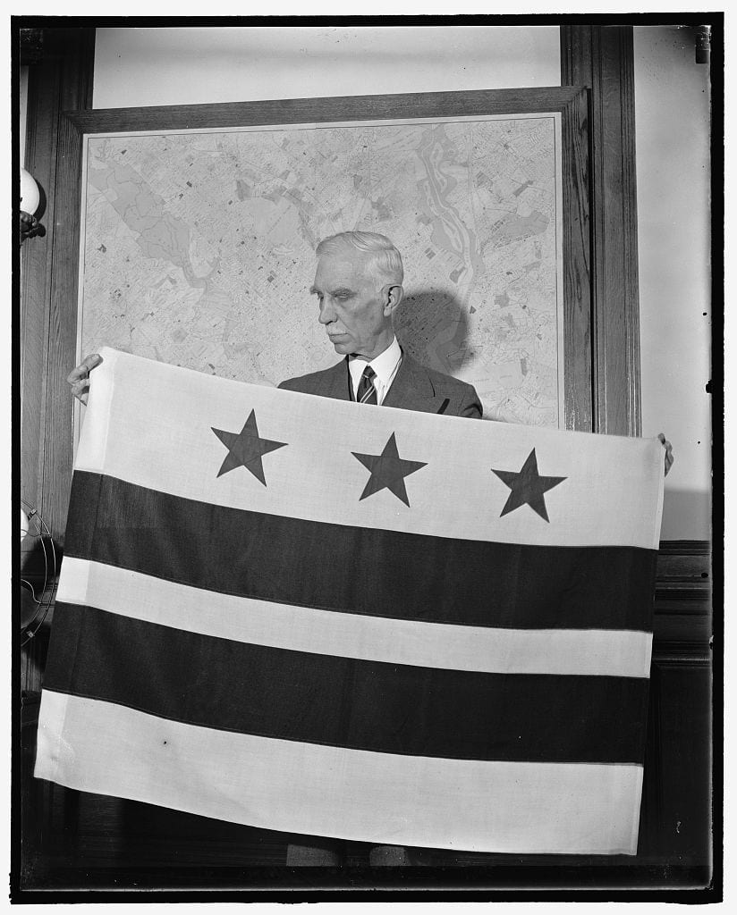 D.C. Commissioner, Melvin Hazen, who chose the design, is pictured with the new flag October 17th, 1938 (Library of Congress)