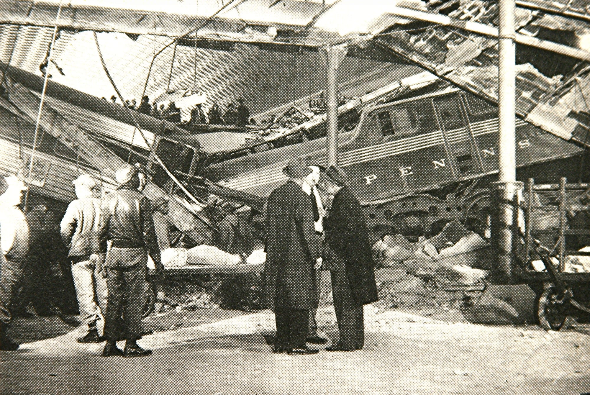 Officials inspect the wrecked train that had crashed through the floor of the concourse. (Photo courtesy of Trains Magazine, August 1953)