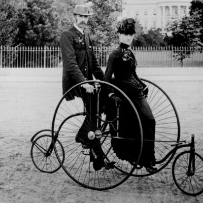 Smartly dressed couple seated on an 1886-model bicycle for two. The South Portico of the White House, Washington, D.C., in the background. 77-RP-7347-4. (National Archives)