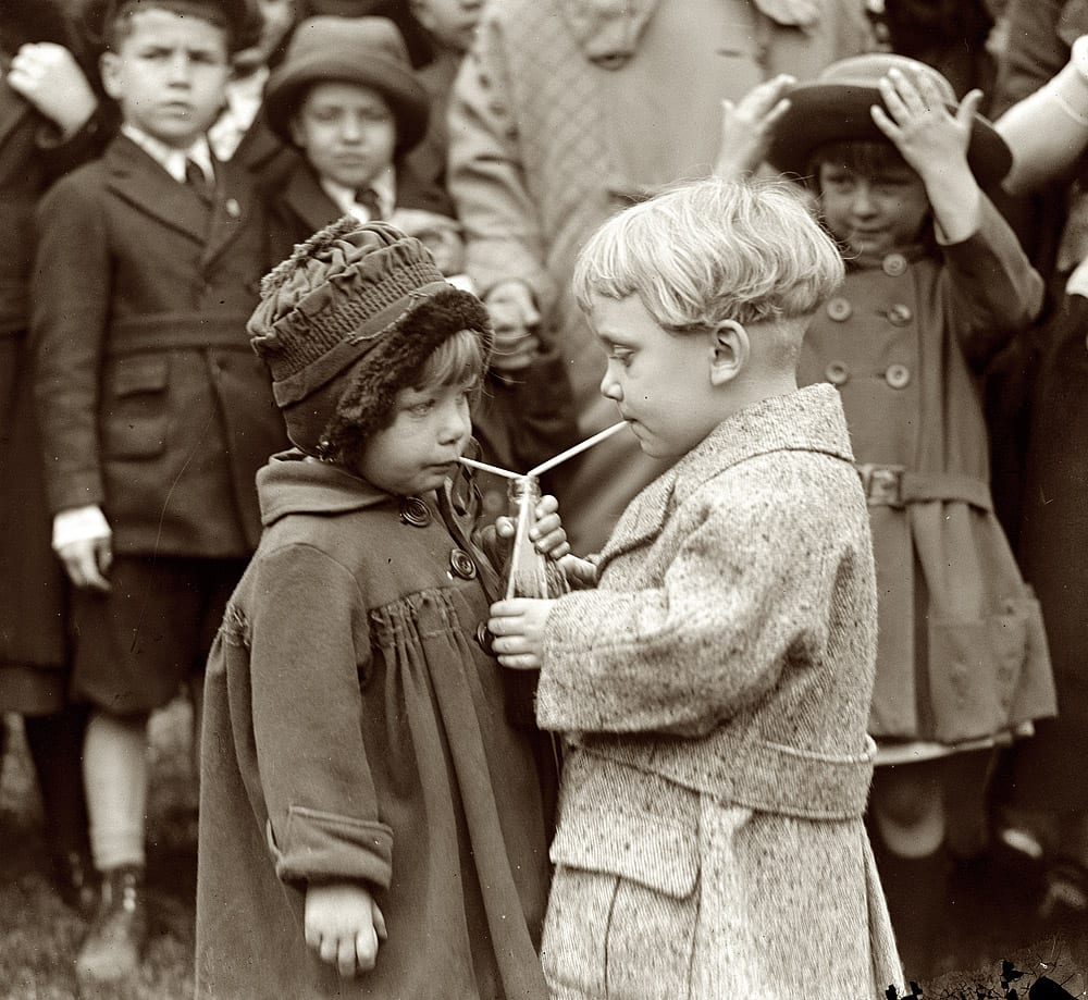 Two kids sharing one soda