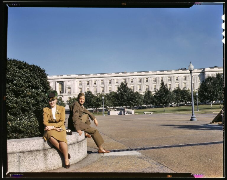 """1943. On maneuvers in wartime Washington. """"A soldier and a woman in a park, with the Old [Russell] Senate Office Building behind them."""" 4x5 Kodachrome transparency, photographer unknown. Office of War Information."""