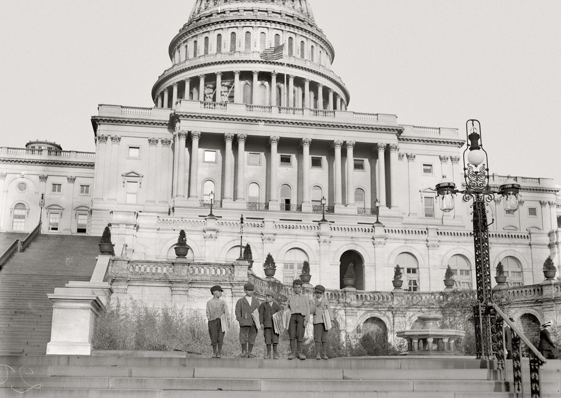 """April 11, 1912. Washington, D.C. """"Group of newsies selling on Capitol steps. Tony Passaro, 8 yrs. old, 124 Schottes Alley N.E.; Dan Mercurio, 9 yrs. old, a chronic truant, 150 Schottes Alley; said he made 8 cents to-day. Joseph Tucci, 10 years old, 411½ 5th St. N.E.; Peter Pepe, 10 yrs. old, 24 Wonders Court; John Carlino, 11 yrs. old."""" Photograph and caption by Lewis Wickes Hine."""