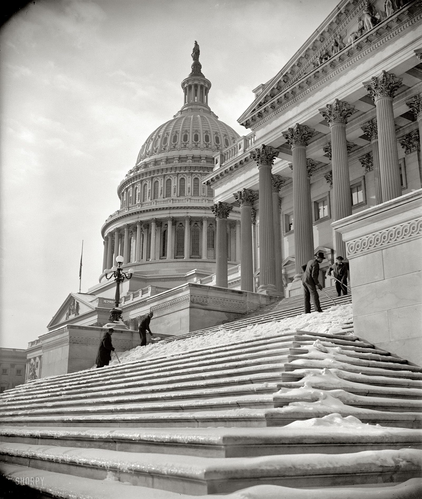 "January 14, 1939. ""National Capital digs out after storm. Nearly five inches of snow blanketed Washington yesterday, followed by sleet. Icy steps made the going to and from the Capitol difficult until workmen arrived this morning and scraped away the menace."" Harris & Ewing Collection glass negative"