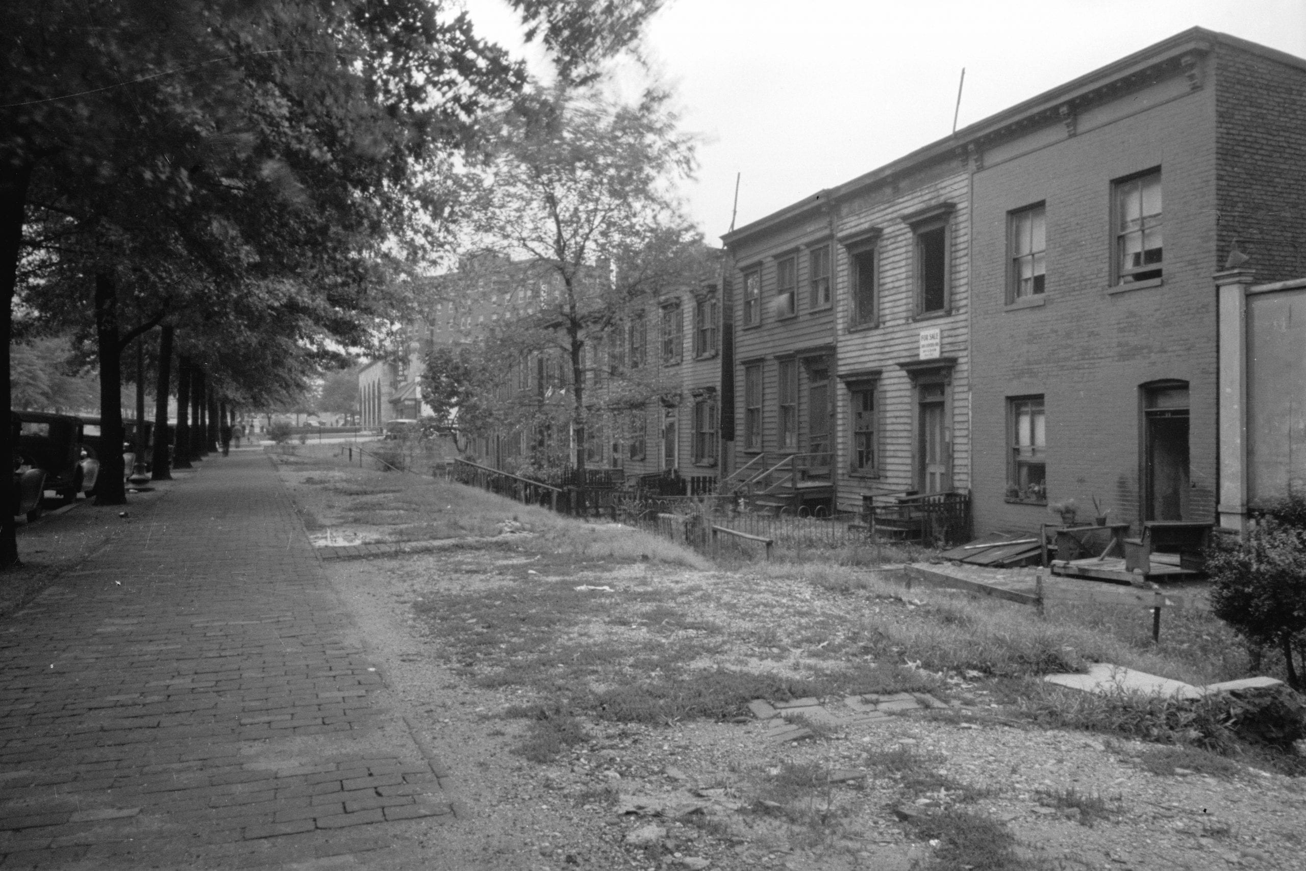 Section of Massachusetts Avenue showing block of shabby houses with outside toilets and water supply