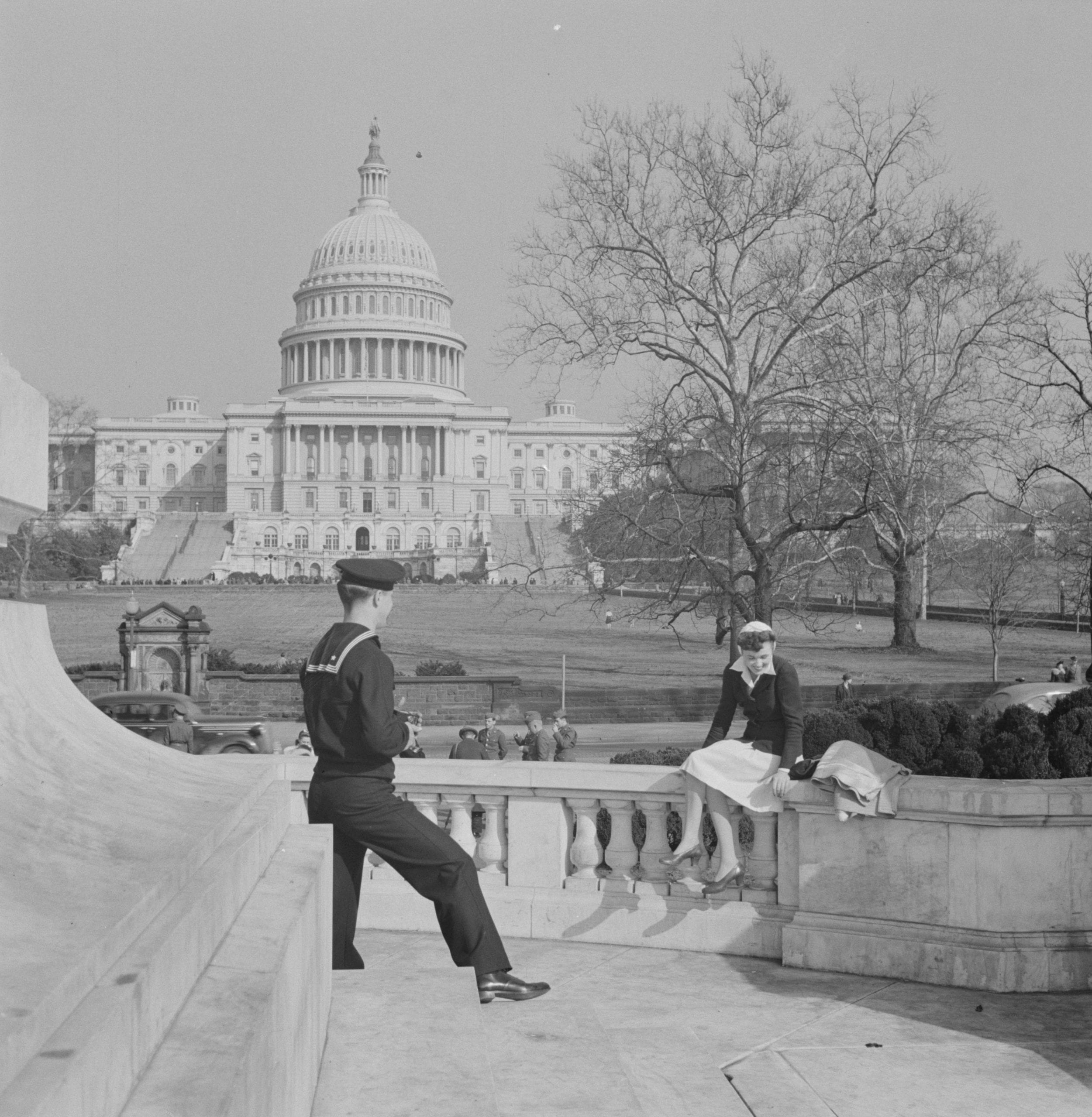 Washington, D.C. Sailor taking a picture of his girlfriend at a monument in front of the Capitol on a Sunday afternoon