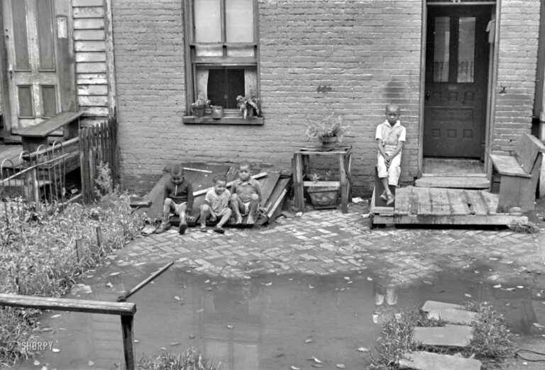 """September 1935. A closeup of the Washington, D.C., row house seen here over the weekend. """"Front of old brick structure in section near Union Station. Land is low here and water collects in front and backyard after a rain and remains for many days. Entrances to privies are usually under water. Interior of homes similar in shabbiness to exterior."""" 35mm nitrate negative by Carl Mydans for the Resettlement Administration."""