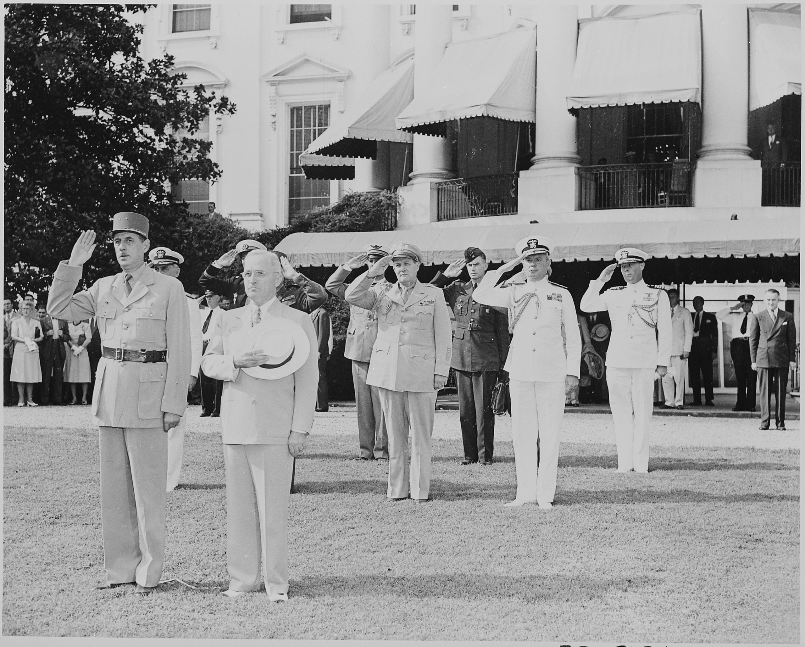 Photograph of President Truman and French President Charles de Gaulle, during welcoming ceremonies on the White House lawn, with officers saluting in the background. (August 22nd, 1945)