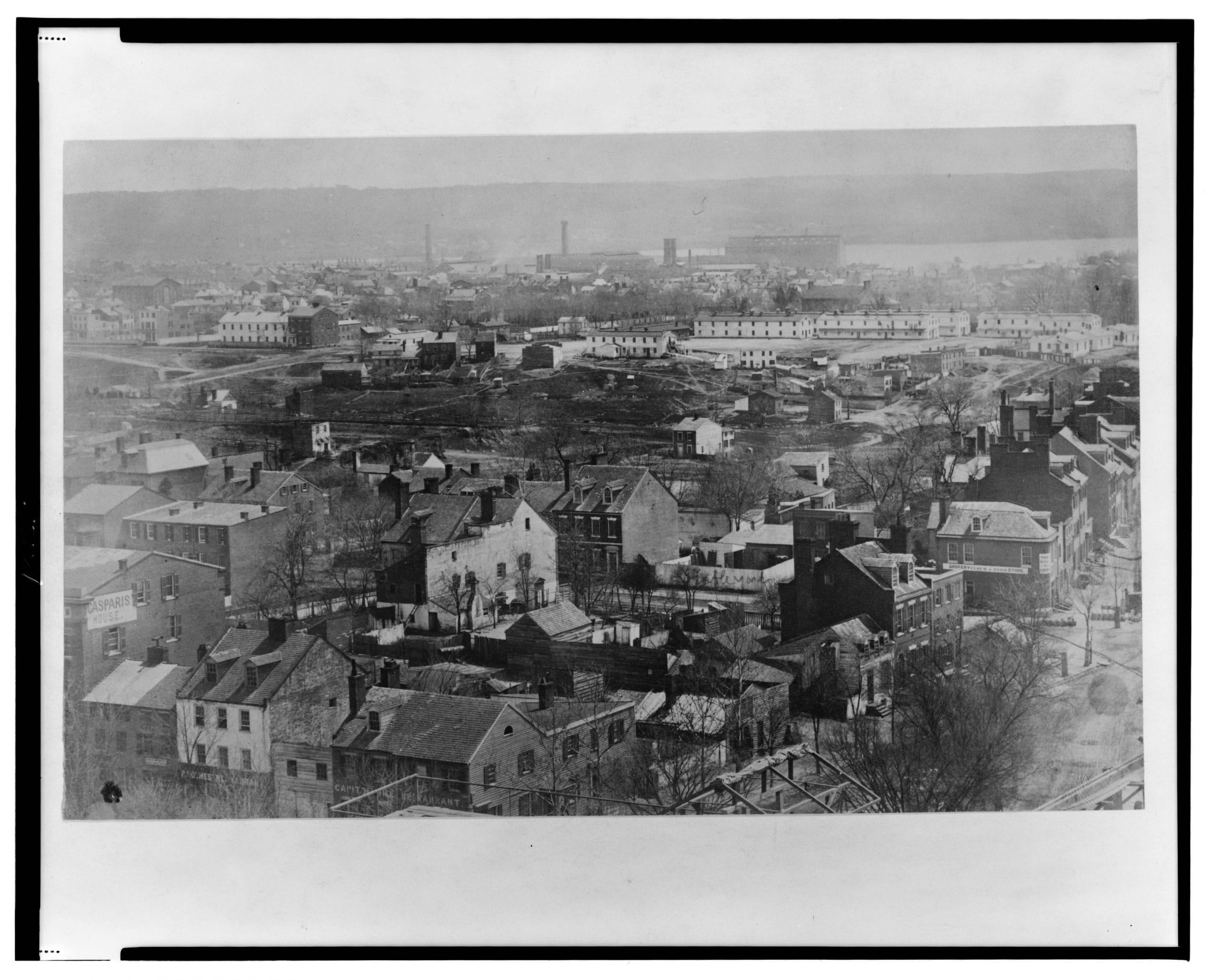 """Southeast view with New Jersey Ave. on the right and A Street and B Street (i.e., Independence Ave.) in the foreground; view includes the Washington Navy Yard, the Eastern Branch (i.e., Anacostia River), the Ebenezer United Methodist Church (i.e., Mount Joy Baptist Church), """"Duddington"""" house, temporary government(?) wooden buildings, the Casparis House, Capitol Hill Restaurant and the Holmes Restaurant."""