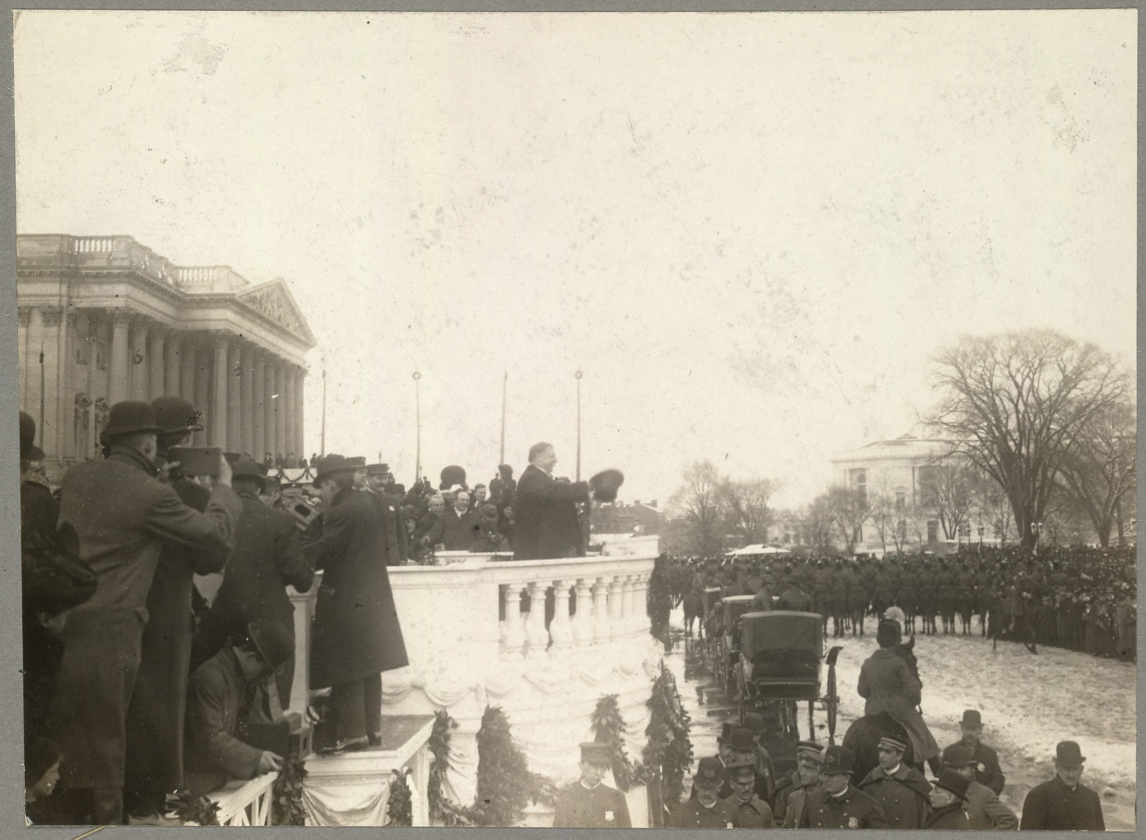 Side view of Taft on balustrade in snow, with top hat in hand, gesturing to crowd before him on grounds of east front of Capitol, with photographers at left.