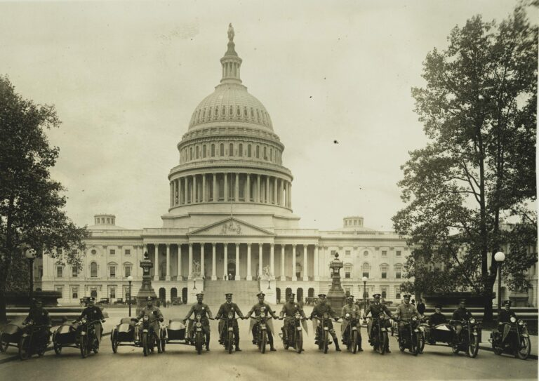 "Photograph shows a group of motorcycle policemen, from left to right: ""Sergt. J.E. Boyle, L.F. Reilly, W.D. Vaughn, F.S. Tyser, L.D. Redman, D.E. Gailmore, G.P. Waite, R.H. Mansfield, G.M. Little, A. Shockey, W.C. Lewis, [and] Capt. J.A. Abbott"" with view of the U.S. Capitol in the background."
