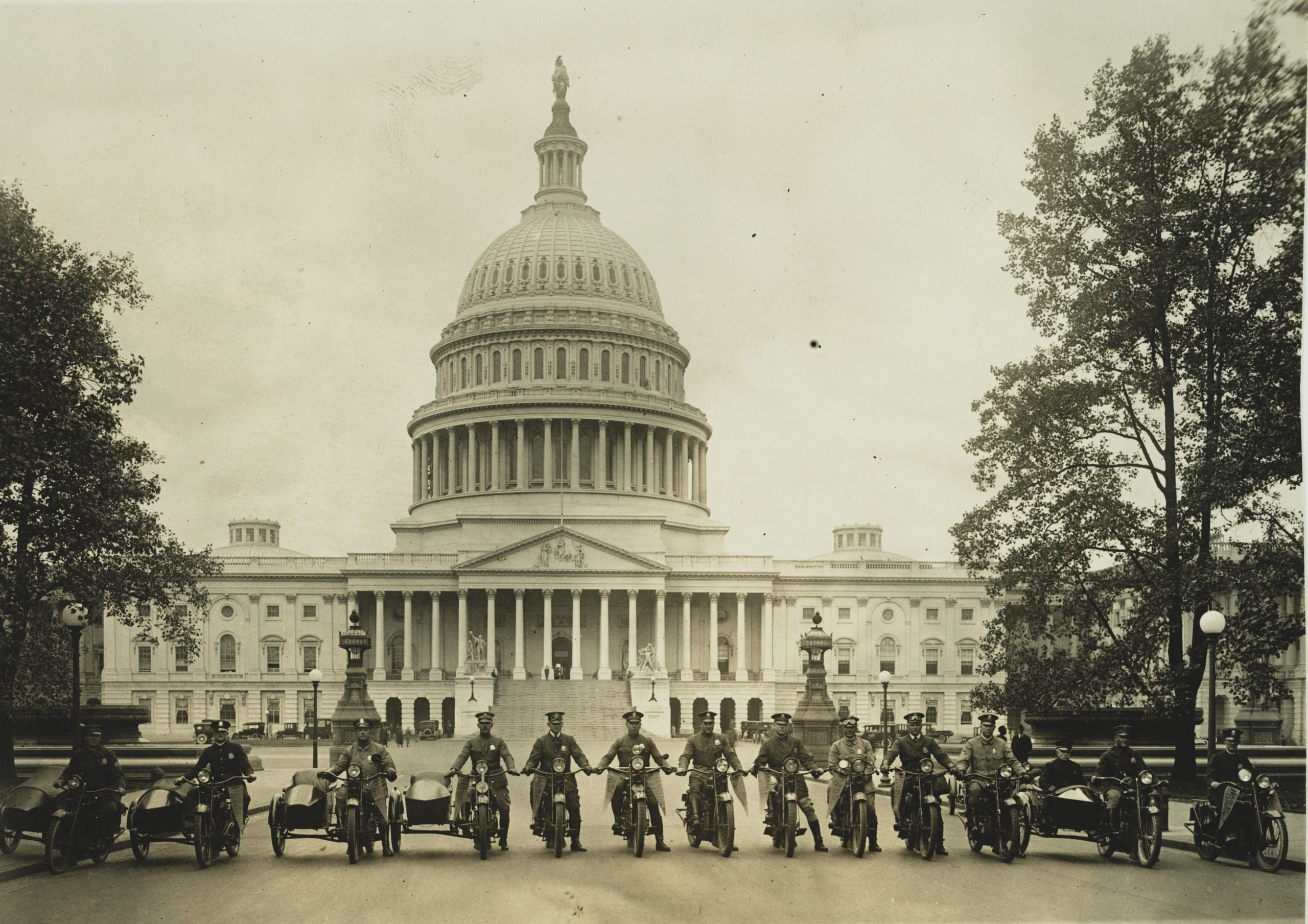 """Photograph shows a group of motorcycle policemen, from left to right: """"Sergt. J.E. Boyle, L.F. Reilly, W.D. Vaughn, F.S. Tyser, L.D. Redman, D.E. Gailmore, G.P. Waite, R.H. Mansfield, G.M. Little, A. Shockey, W.C. Lewis, [and] Capt. J.A. Abbott"""" with view of the U.S. Capitol in the background."""