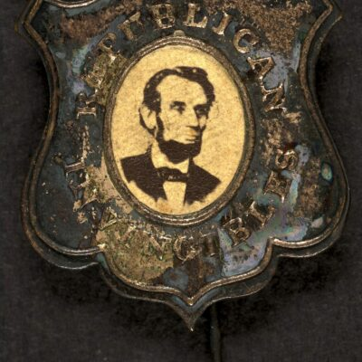 Political campaign button for 1864 presidential election showing bust portrait of Abraham Lincoln, facing right (possibly Wenderoth & Taylor photo); metal shield with oval window and with pin fastener attached.
