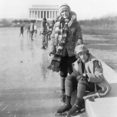 Abbey Jackson, seated, and Celene DuPuy ice skating on reflecting pool, with Lincoln Memorial in background