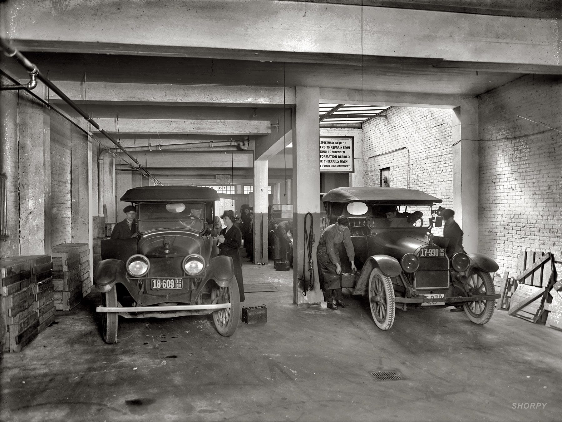"""District of Columbia, 1919. Willard Service Station, Washington Battery Co., 1623 L Street. The sign: """"We respectfully request customers to refrain from talking to workmen. Any information desired will be cheerfully given out by floor superintendent."""" National Photo Company glass negative."""