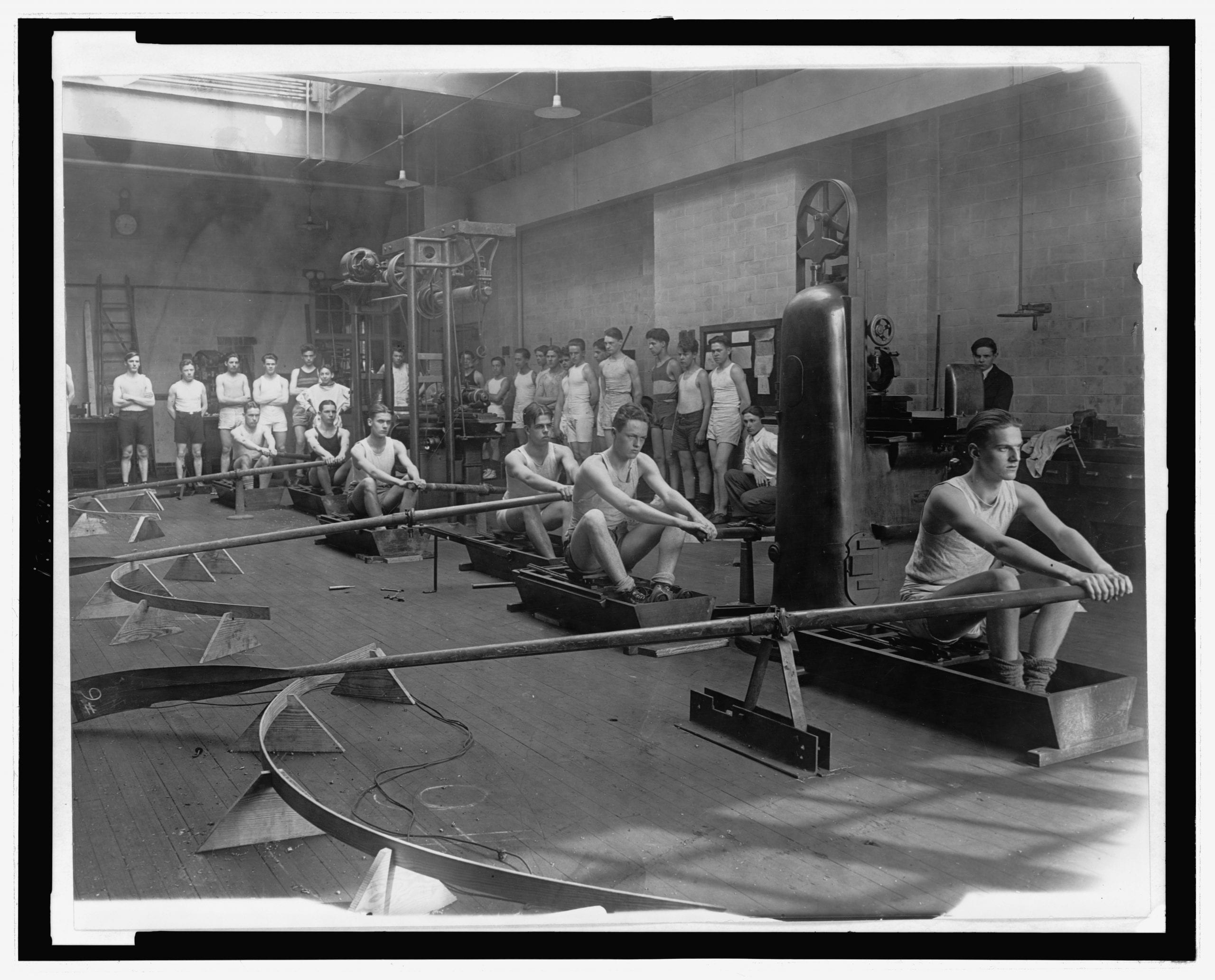 Photograph shows young men practicing rowing on stationary machines in a gynmasium as others wait their turn to practice. Pictured rowing are: Stanley Durkee, Arthur Dorton, Ronald Collauday, Donald Kline, William Stewart and Elkin Hale. (1919)