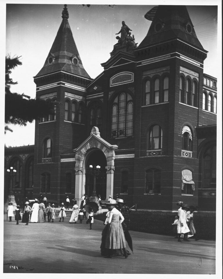 At the turn of the century, visitors are entering and leaving the United States National Museum Building, now Arts and Industries Building, via the North Entrance. The entrance has glass doors, which dates it to before the Hornblower and Marshall designed doors installed between 1902-1907
