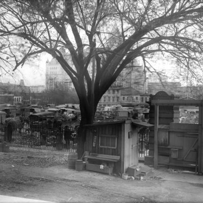 View of the Center Market of Washington, D.C. from the north entrance of the United States National Museum, now the National Museum of Natural History, on October 16, 1909. There are horse-drawn carriages and carts, vendors, storefronts, and the Old Post Office is in background, center. In the foreground is the large wooden gate to the grounds of the Natural History Building and a small guard house next to it