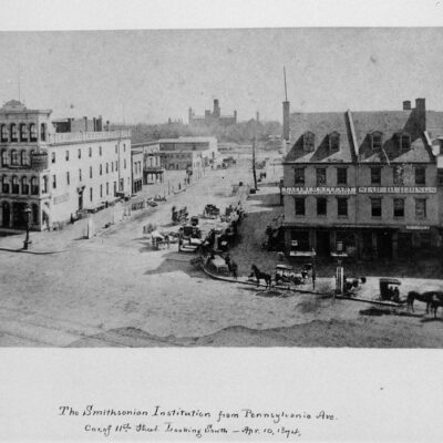 "Looking south from the corner of Pennsylvania Avenue and 11th Street, the silhouette of the Smithsonian Institution Building is seen in the distance. The photograph, taken by William Henry Holmes and signed ""W.H.H. Phot.,"" shows horse-drawn carriages along the avenue of storefronts. Above the first building to the right of 11th Street, the sign reads ""Latimer & Cleary Auction and Commission Merchants"", the next building has a sign ""Star Buildings,"" and the third building ""Metropolitan."""