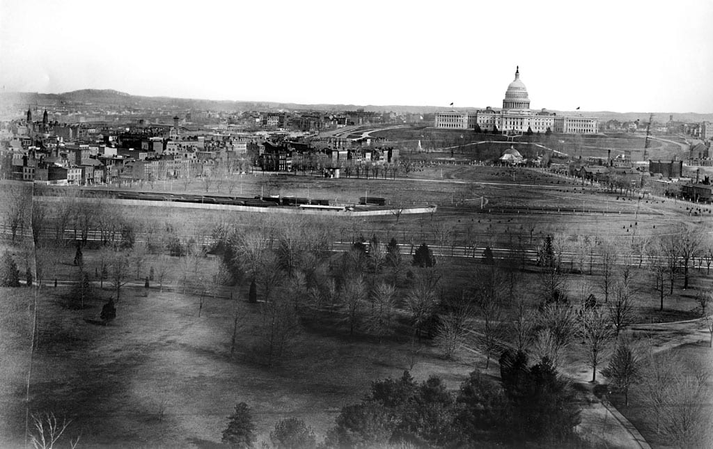 Looking toward the west side of the United States Capitol building, a panoramic view of the city of Washington, D.C. shows the Mall area in the foreground before the railroad tracks were removed. A train is visible on the tracks. The domed structure in front of the Capitol is the Botanic Garden original octagonal greenhouse of 1859 and behind it the central pavilion added after the Civil War. The buildings were razed in 1932. The Botanic Garden was on a site previously occupied by the Columbian Institute for the Promotion of Arts and Sciences in Washington, D.C.
