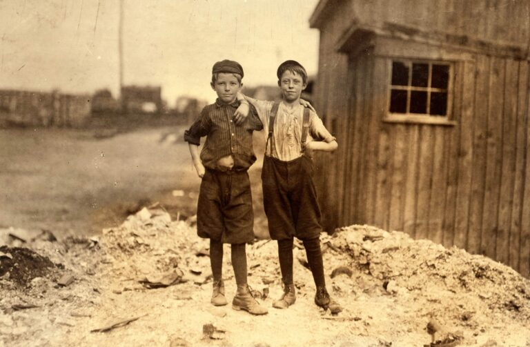 Two young carrying-in boys in Alexandria (Va.) Glass Factory. Frank Clark (on left) 702 N. Patrick St., could neither read nor write, having been to school only a few weeks in his life. Two older brothers work in glass factory, and his father is a candy maker. Frank is working on night shift this week. Ashby Corbin (on right), 413 N. St. Asaph St. Has had only four terms of schooling. See also photos and labels 2260 to 2271. Location: Alexandria, Virginia.