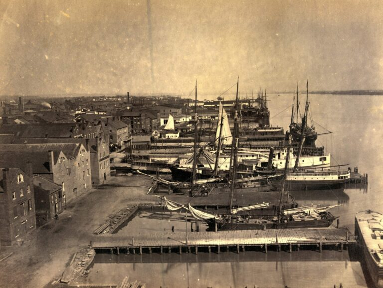Photograph shows cargo ships at the wharf in Alexandria, Virginia from Pioneer Mill, which was six stories high.