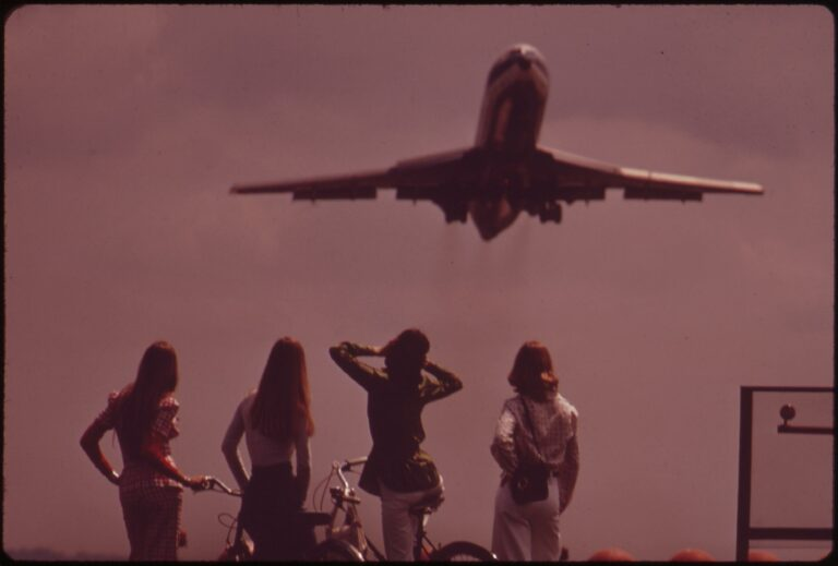 One Of The Bicyclists Holds Her Ears Against The Roar Of The Jet, Taking Off From National Airport, May 1973
