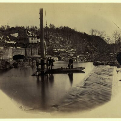 Entrance to Washington Water Works, Great Falls, Potomac River - Photograph shows two men standing in a small flat boat near the spillway.