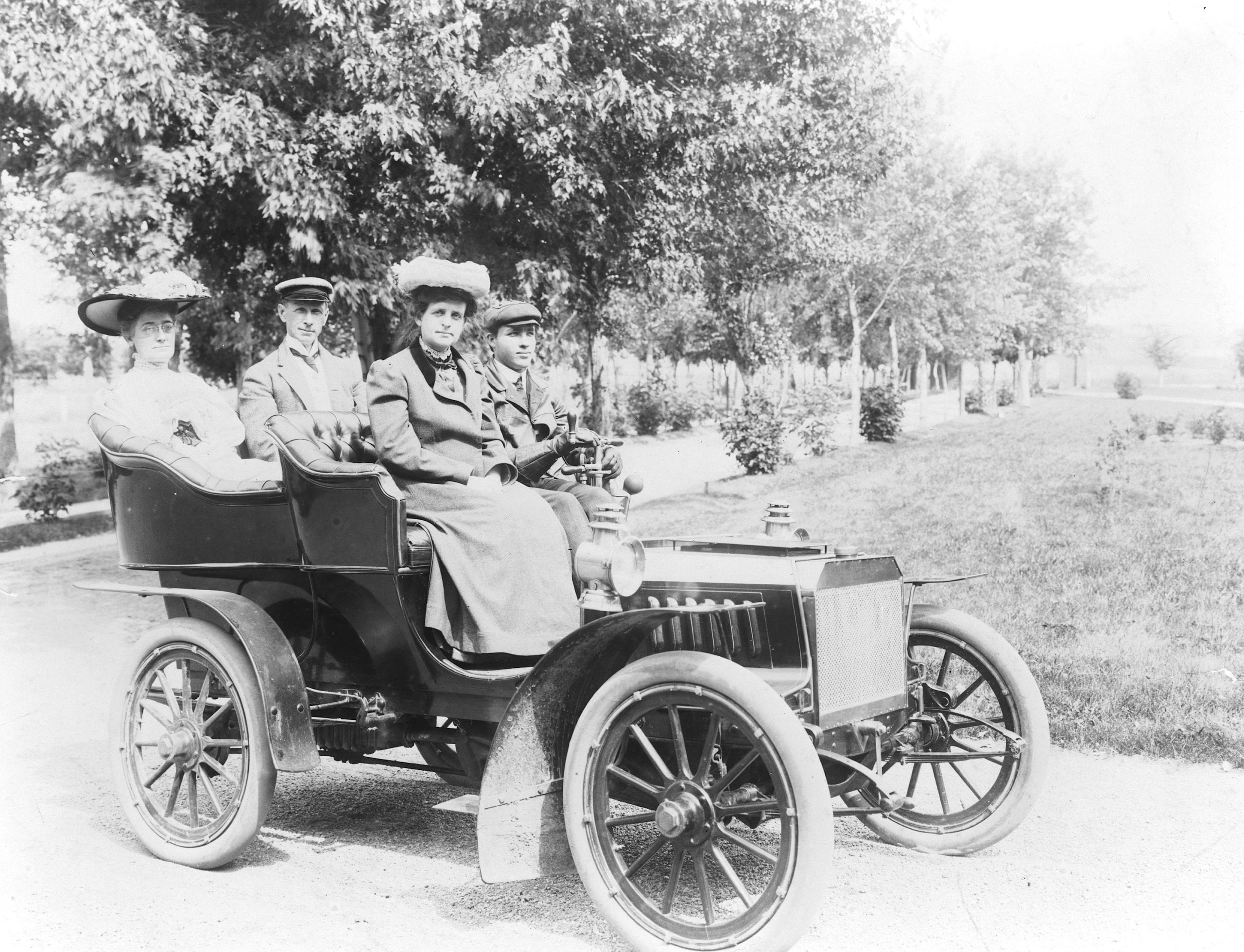Frances Benjamin Johnston seated with three other people in automobile