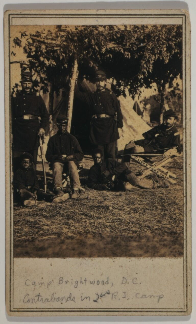 Capt. B.S. Brown (left); Lt. John P. Shaw, Co. F 2nd Regt. Rhode Island Volunteer Infantry (center); and Lt. Fry (right) with African American men and boy.