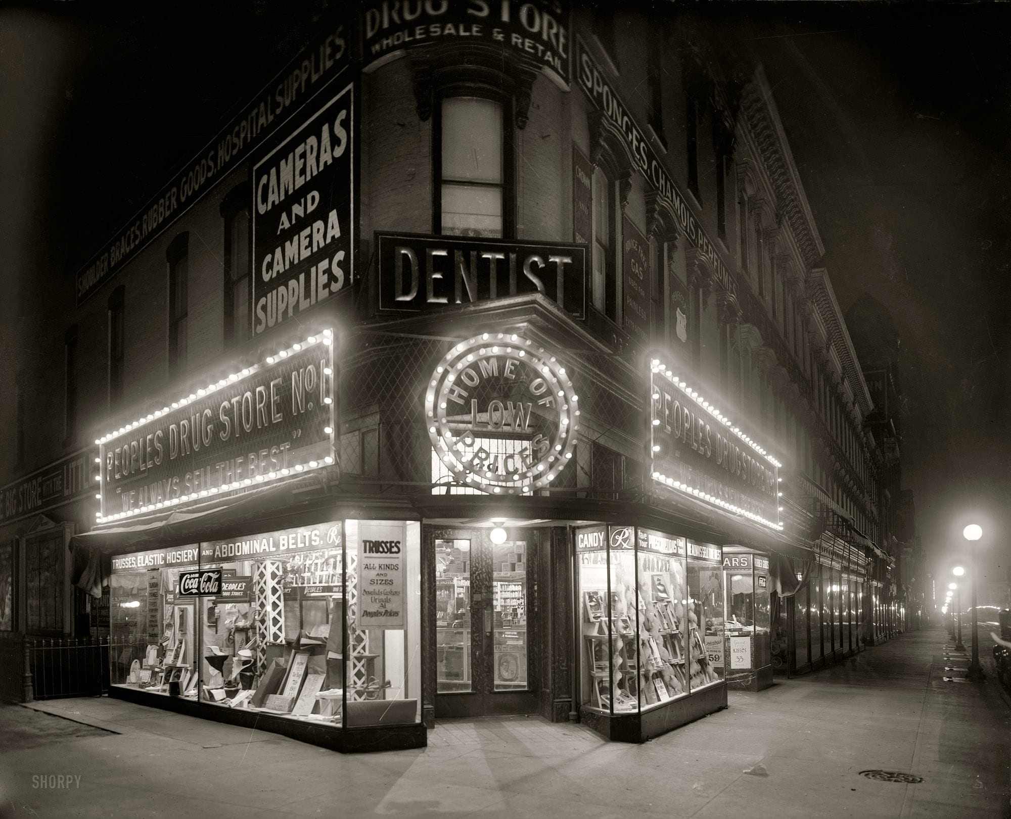 "Washington, D.C., circa 1921. ""People's Drug Store, Seventh & K, night."" With a lurid display of ""trusses and rubber goods."" National Photo Co."