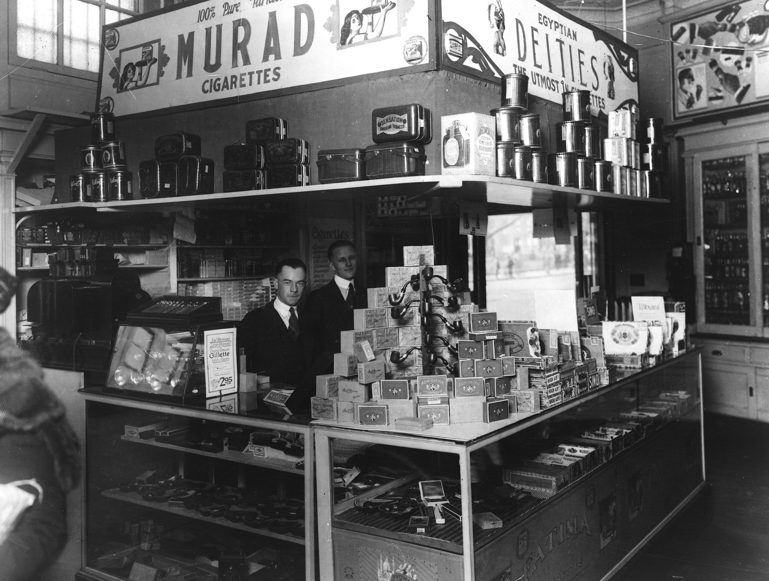 Interior of People's Drug Store, 7th and K Streets, Washington, D.C., with employees behind counter with display of smoking products including pipes, cigars, tobacco, and cigarettes (1920s)