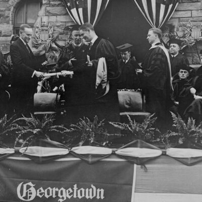 Calvin Coolidge, President of the United States, presents an honorary degree to Governor William S. Flynn of Rhode Island at the Georgetown University commencement. Pictured, left to right: Pierce Butler, Associate Justice of the Supreme Court; President Coolidge; John B. Creeden, S.J., President of Georgetown University; Governor Flynn; Walter J. O'Connor, University Registrar; and Andrew L. Bouwhuis, S.J.