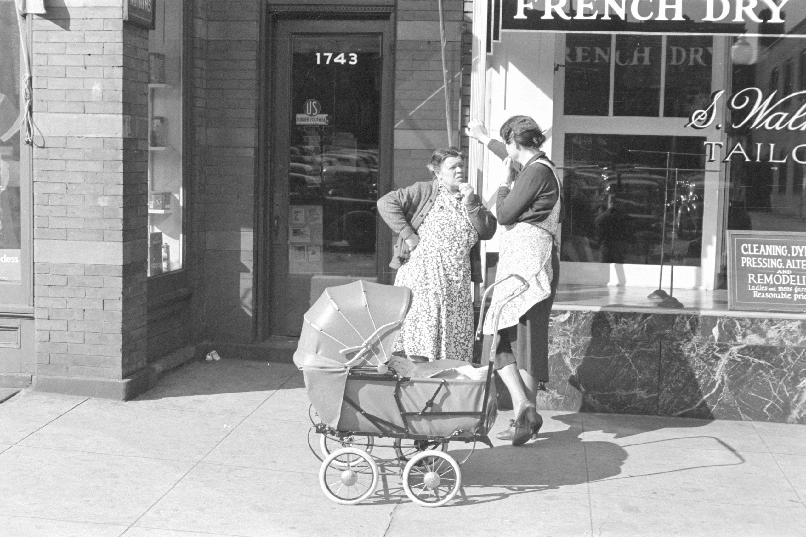 woman and carriage in front of store