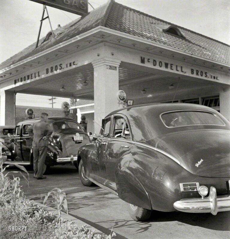 """Washington, D.C. """"At 7 a.m. on June 21, 1942, the day before stricter gas rationing was enforced, cars were pouring into this gas station on upper Wisconsin Avenue."""" If they still made cars that looked like this Packard, we'd run right out and buy one. Photo by Marjory Collins for the Office of War Information."""