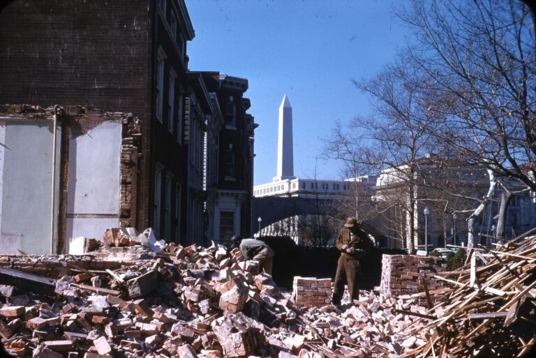 "Demolition of buildings on the corner of 11th Street and Virginia Avenue SW. View northwest over the Agriculture Department Building to the Washington Monument (1959). Garnet W. Jex ""Southwest Redevelopment"" Slide Collection, HSW."