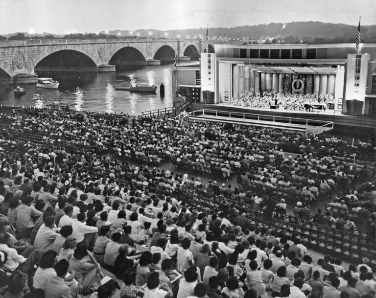 Crowd on Watergate steps watching performance on barge at edge of Potomac River (ca. 1956). Burdell Wright, Jr. Photograph Collection