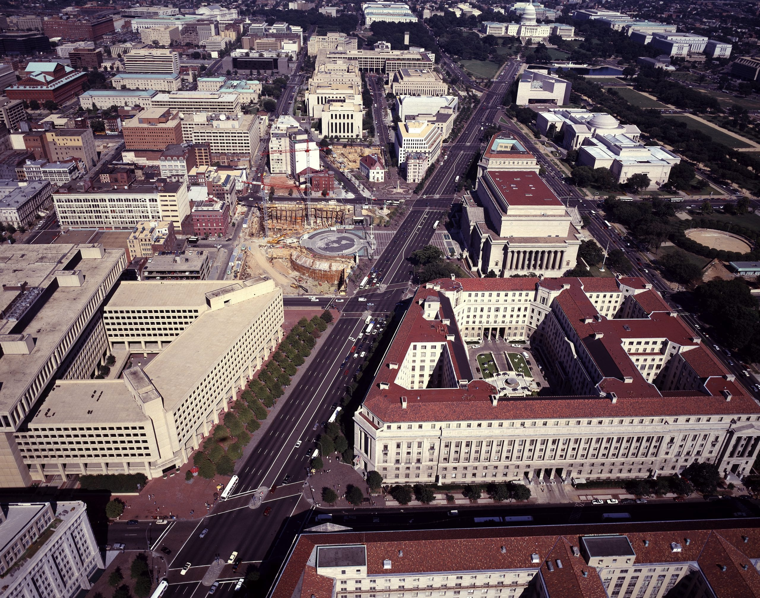 """Aerial view of Washington, D.C., offering a good view of the """"triangle"""" in the Federal Triangle row of federal office buildings.  Image taken during the 1980s.  Note the Navy Memorial construction."""