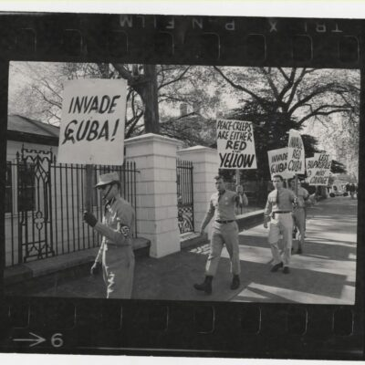 "Demonstrators from a broad political spectrum picket outside the White House during the height of the Cold War confrontation between the United States and the Soviet Union over the placement of missile silos in Cuba. The Cuban missile crisis demonstration attracted elements on the fringe of American society as evidenced by the last panel frame showing members of an American neo-Nazi group protesting President John F. Kennedy's ""soft"" stance on Cuba."