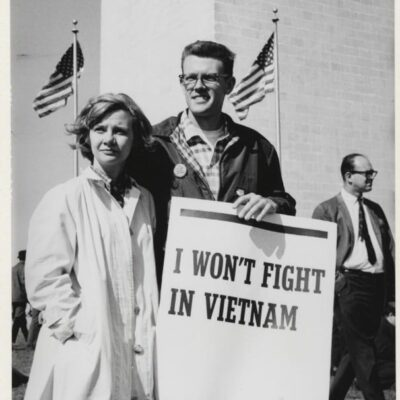 """The clean-cut collegiate looks of these two young peace activists do not fit the common stereotype of the long-haired radicals and """"peaceniks"""" who protested against the escalating war in Southeast Asia. They were joined by several hundred thousand anti-war protestors who descended upon the nation's capitol to dissent against what they believed was an immoral war."""