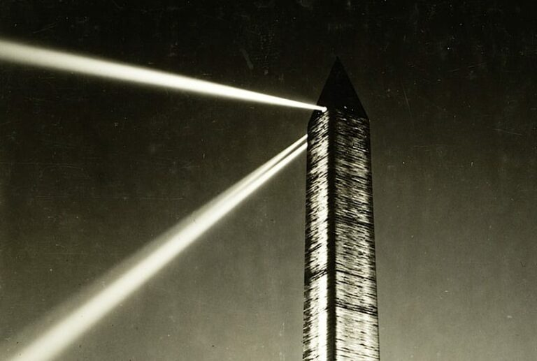 Photograph shows lights beaming from the top of the Washington Monument at night, also large lights on the ground, directed up, illuminating the sides.