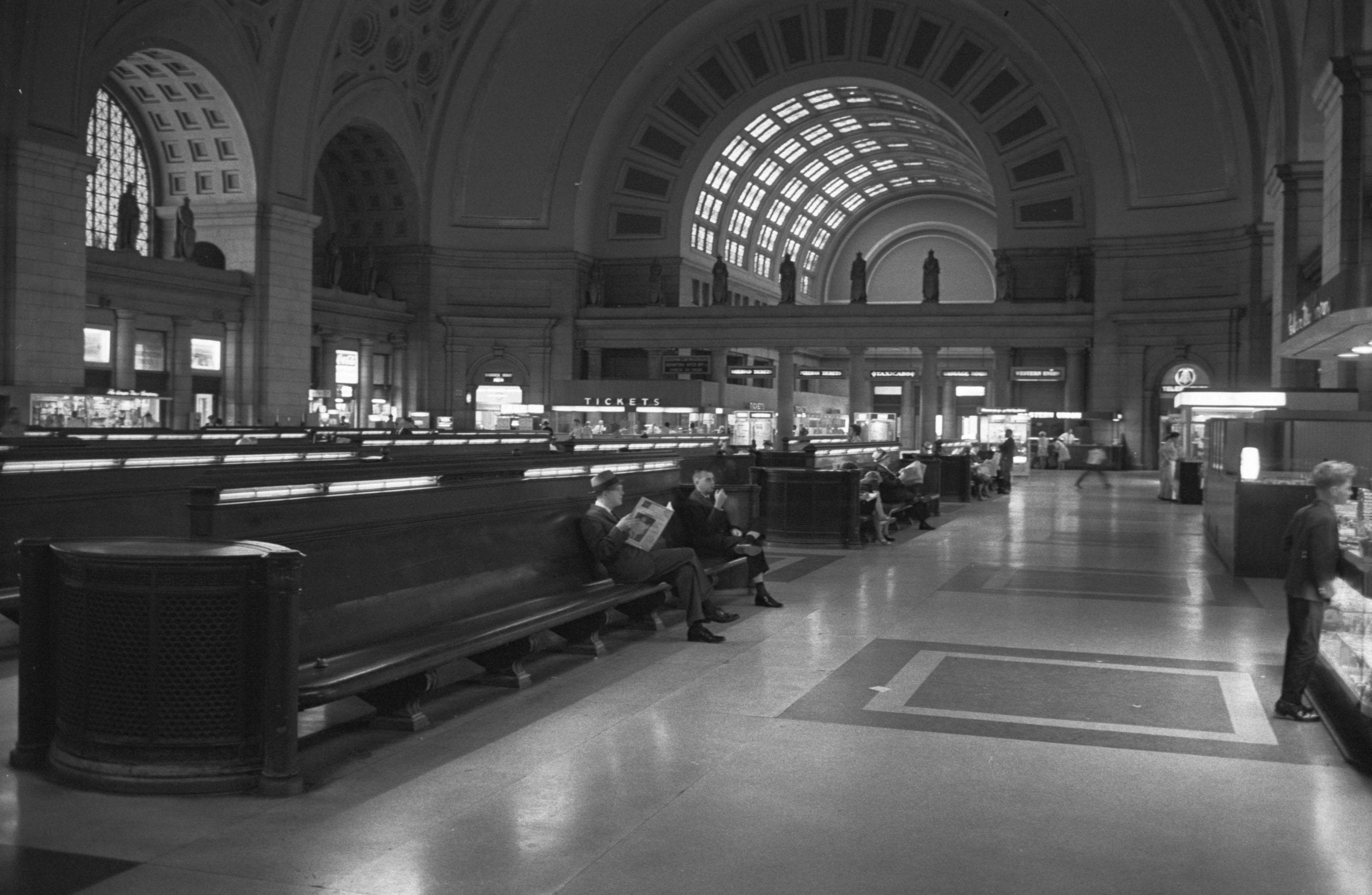 Passengers seated in long benches in the waiting room of Union Station, Washington, D.C.