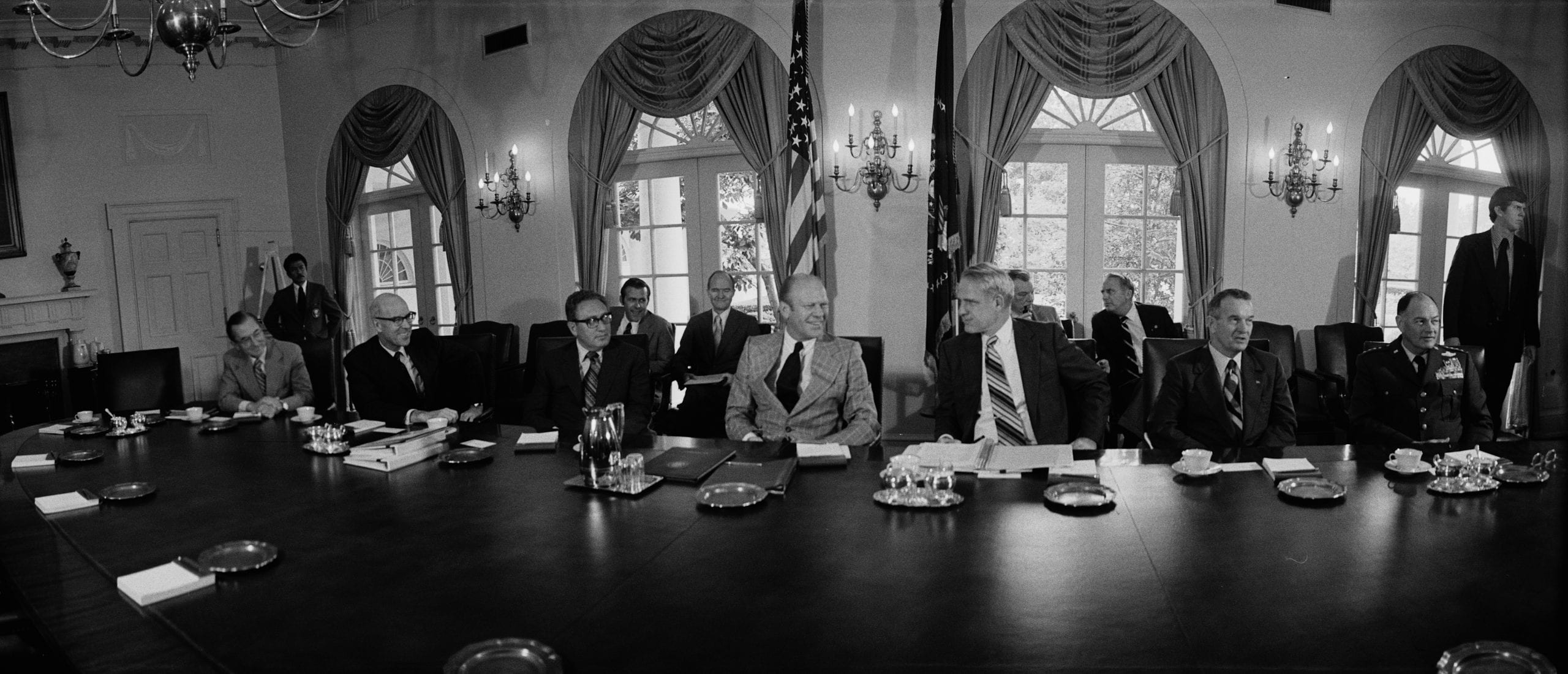 Photographic negative showing President Ford seated at a table with William E. Colby, Director of CIA; Robert S. Ingersoll, Deputy Secretary of State; Henry Kissinger, Secretary of State; James R. Schlesinger, Secretary of Defense; William P. Clements, Jr., Deputy Secretary of Defense; George S. Brown, Chairman of Joint Chiefs.