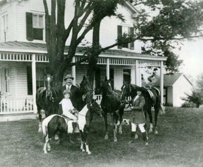 "Andrew J. Cummings, Jr., on his pony ""Sugar,"" Andrew J. ""Cy"" Cummings, and Zelpha Cummings, c. 1920-1923. From a print lent by Andrew J. Cummings, Jr. CCHS 2008.12.06."