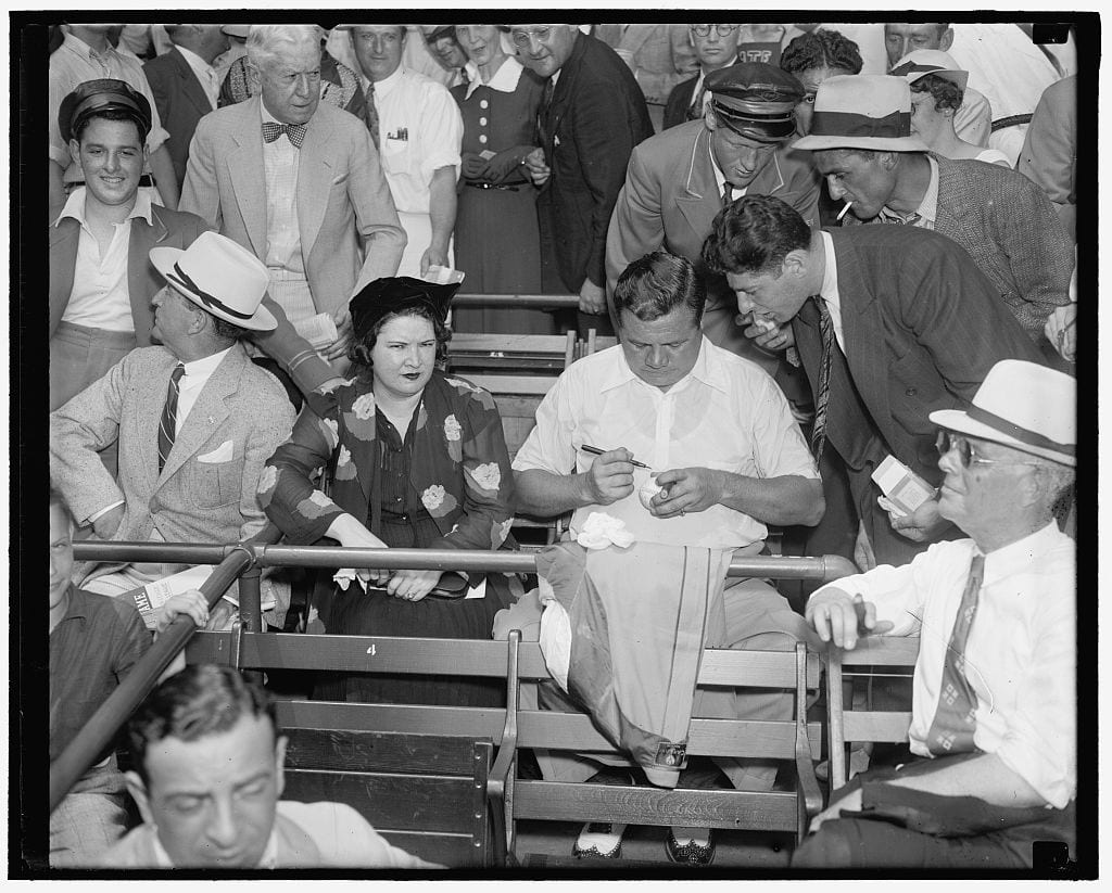 Babe Ruth signs autographs