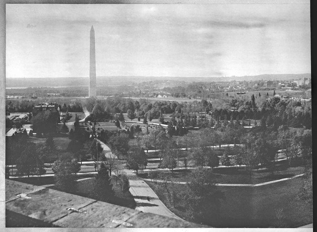 First in a series of four panoramic photographs of Washington, D.C., from left to right taken from a tower in the Smithsonian Institution Building. Looking toward the Washington Monument, the street in the foreground running from left to right is 12th Street, N.W., which was later tunneled under the Mall. The old Department of Agriculture Building is visible on the left beside 14th Street, N.W. The large grassy area on the right is the Ellipse