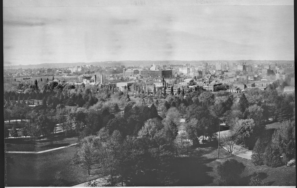 Second in a series of four panoramic photographs of Washington, D.C., moving from left to right, taken from a tower in the Smithsonian Institution Building. The Mall is in the foreground covered with trees with the buildings of the City of Washington beyond. On the left is the Ellipse just beyond the trees and the large building behind it is the State, War and Navy Building, now known as the Old Executive Office Building