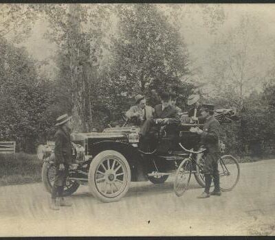 Town Marshall, Charles Collins, ticketing a car along Conduit Road (MacArthur Boulevard). Note the 12MPH limit. ca. 1907